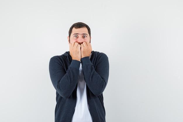 Junger mann beißt fäuste emotional in t-shirt, jacke und ängstlich, vorderansicht.