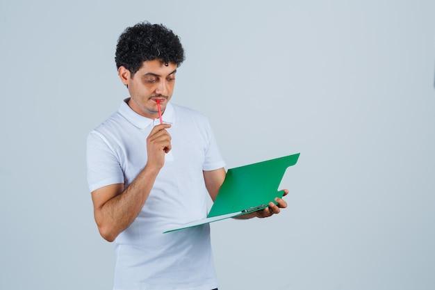 Junger mann beißt stift, hält notizbuch und sieht es in weißem t-shirt und jeans an und sieht nachdenklich aus. vorderansicht.