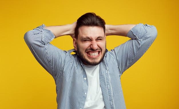Junger mann beißt zähne in der verzweiflung isoliert zusammen