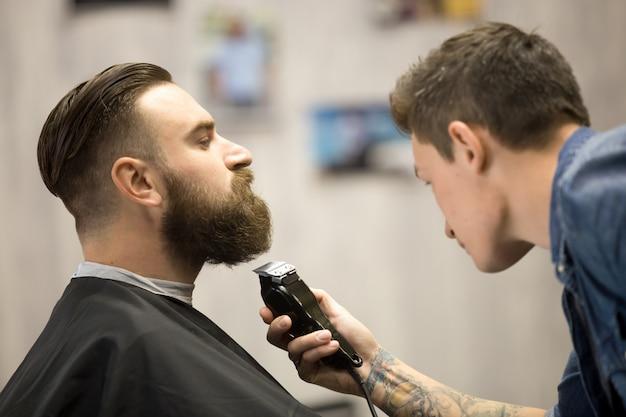 Junger mann bekommt bart grooming am friseursalon