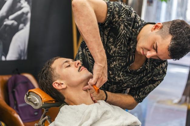 Junger mann bekommt eine altmodische rasur im friseurladen