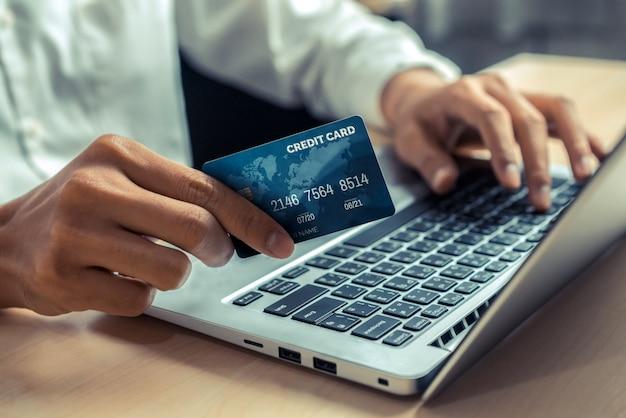 Junger mann benutzt kreditkarte für online-shopping