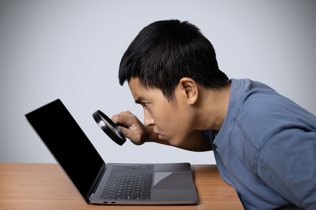 Junger mann beobachtet laptop mit lupe auf grauem hintergrund.