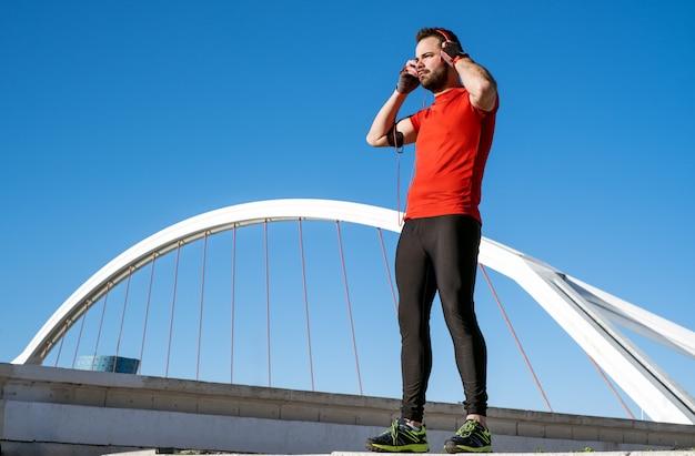 Junger mann bereitet sich vor, mit einem paar kopfhörer vor einer brücke zu rennen