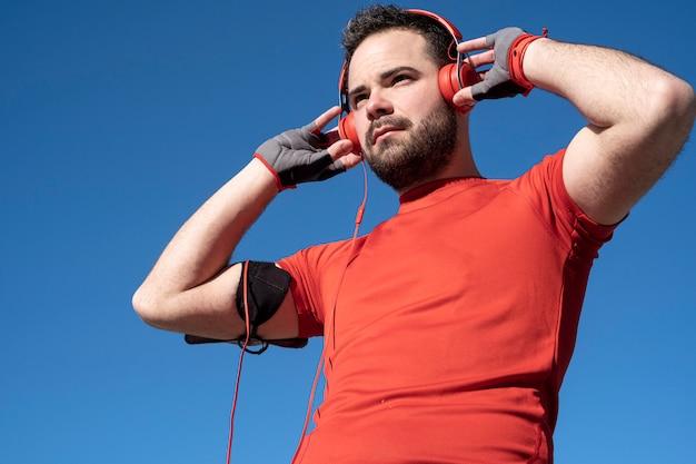 Junger mann bereitet sich vor, mit einem paar kopfhörer zu laufen