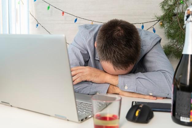Junger mann betrunken im home office nach weihnachtsfeier. der geschäftsmann ist bei der arbeit müde. ein betrunkener mitarbeiter ist nach einer firmenfeier krank.