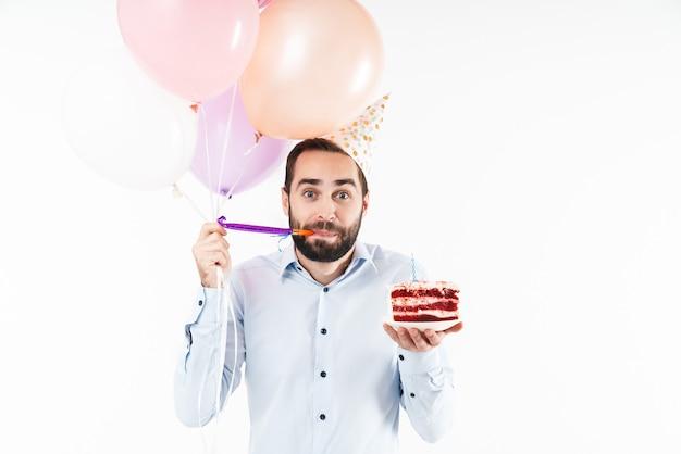 Junger mann bläst partyhorn und hält geburtstagstorte mit luftballons isoliert über weißer wand
