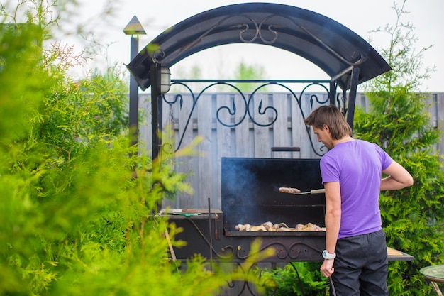 Junger mann brät steaks auf dem grill, der in seinem yard im freien ist