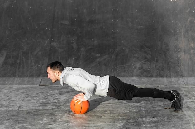 Junger mann, den das handeln drückt, ups auf einen basketball