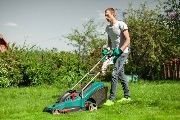 Junger mann den rasen mähen. arbeitskraft, die seine arbeit im hinterhof erledigt.