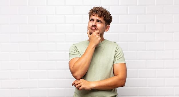 Junger mann denkt, fühlt sich zweifelhaft und verwirrt, mit verschiedenen optionen isoliert