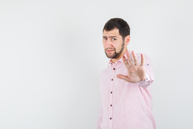 Junger mann, der ablehnungsgeste im rosa hemd zeigt und genervt aussieht