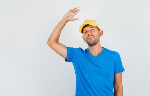 Junger mann, der abschied mit handzeichen im blauen t-shirt sagt