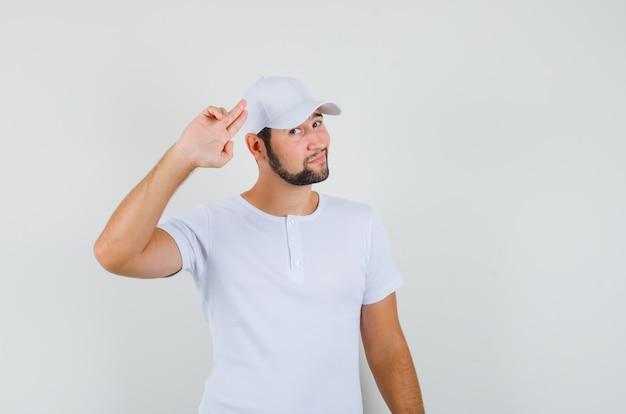 Junger mann, der abschiedsgeste im t-shirt zeigt und entspannt schaut. vorderansicht.
