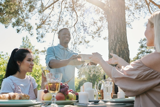 Junger mann der afrikanischen ethnischen zugehörigkeit, der behälter mit essen von den händen seiner freundin über serviertem tisch während des abendessens im freien unter kiefer nimmt