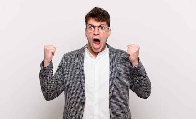 Junger mann, der aggressiv mit einem wütenden ausdruck oder mit geballten fäusten schreit, um erfolg zu feiern