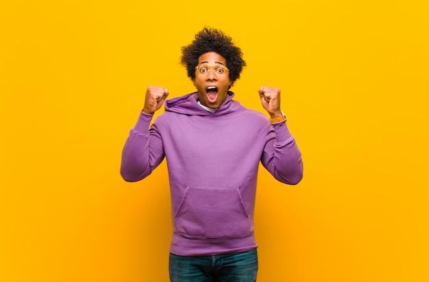 Junger mann, der aggressiv mit einem wütenden ausdruck oder mit geballten fäusten schreit und erfolg über orange wand feiert