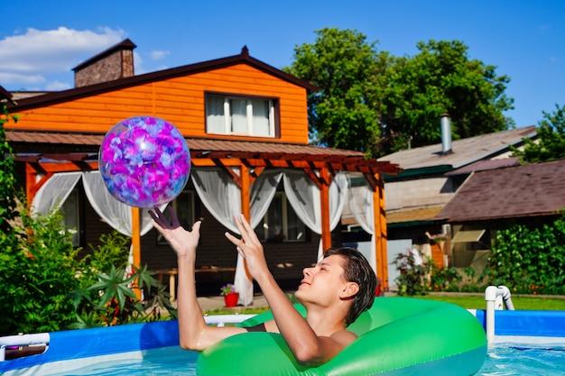 Junger mann, der aktive spiele im pool spielt und einen aufblasbaren ball wirft, sommerspaß und unterhaltung ...