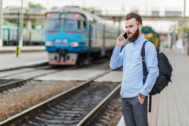 Junger mann, der am bahnhof unter verwendung des mobiltelefons steht