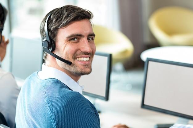 Junger mann, der am computer mit headset arbeitet