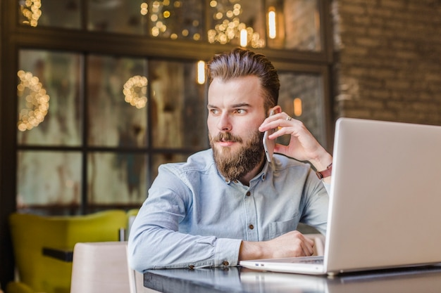 Junger mann, der am handy mit laptop auf schreibtisch spricht