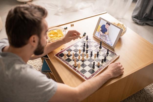 Junger mann, der am kaffeetisch im wohnzimmer sitzt und wartet, wenn konkurrent schach während der online-kommunikation bewegt