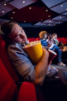 Junger mann, der am kino schläft