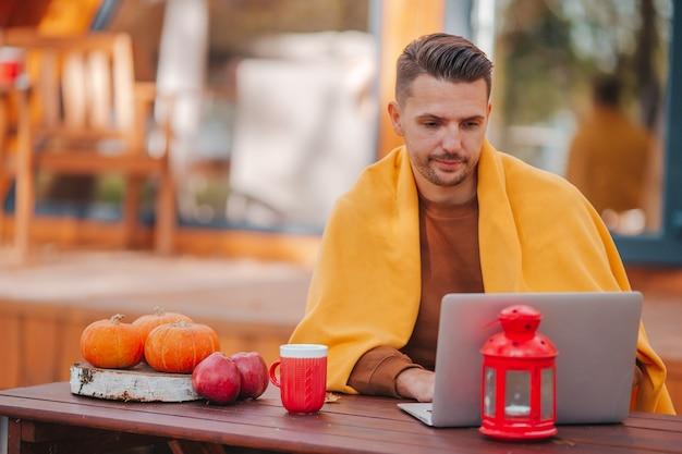 Junger mann, der am laptop arbeitet und kaffee trinkt, der am hölzernen tisch draußen am herbsttag sitzt