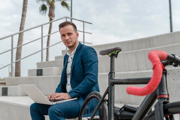 Junger mann, der am laptop neben seinem fahrrad arbeitet