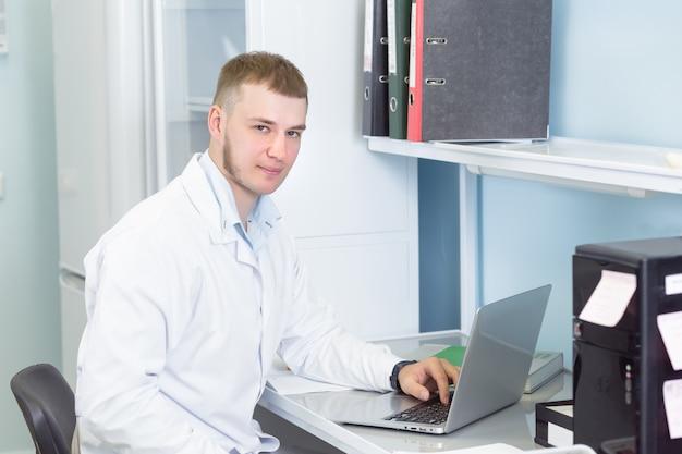 Junger mann, der am medizinischen oder genetiklabor arbeitet