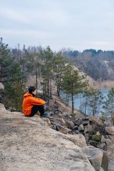 Junger mann, der am rand einer klippe sitzt