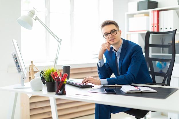 Junger mann, der am schreibtisch im büro sitzt und an computer arbeitet.