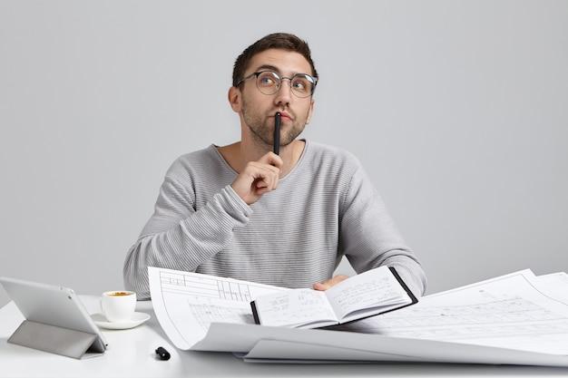 Junger mann, der am schreibtisch sitzt und papierkram tut