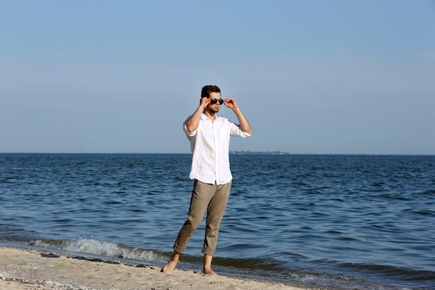 Junger mann, der am strand geht