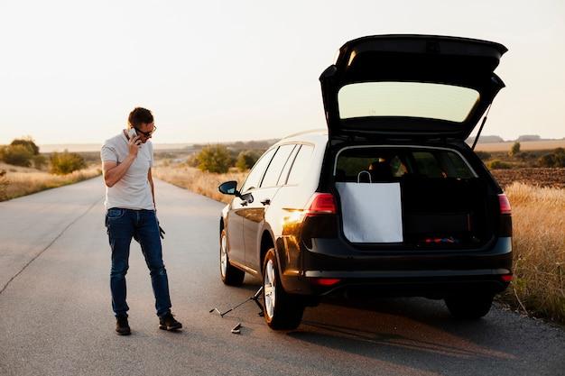 Junger mann, der am telefon durch ein auto spricht