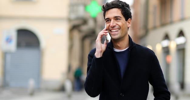 Junger mann, der am telefon im freien spricht