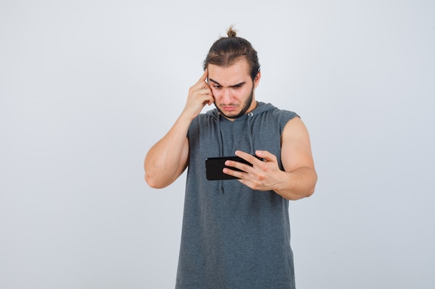 Junger mann, der am telefon im kapuzen-t-shirt schaut und nachdenklich, vorderansicht schaut.