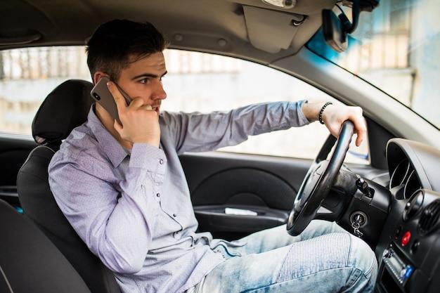 Junger mann, der am telefon spricht, während er sein auto fährt