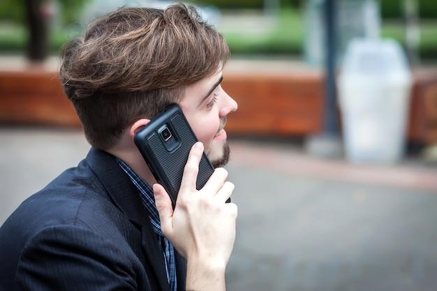 Junger mann, der am telefon und am lächeln spricht