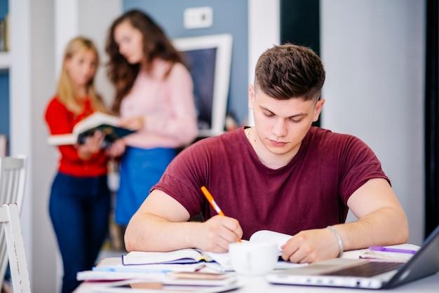 Junger mann, der am tisch studiert