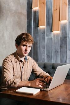 Junger mann, der an dem laptop arbeitet