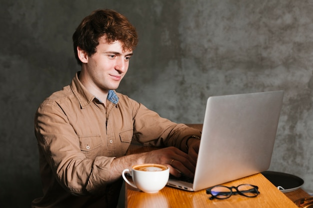 Junger mann, der an dem laptop im büro arbeitet