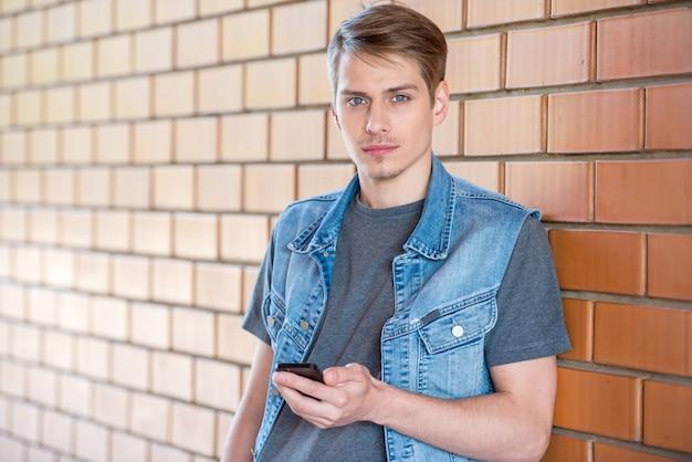 Junger mann, der an der backsteinmauer sich lehnt und telefon hält.