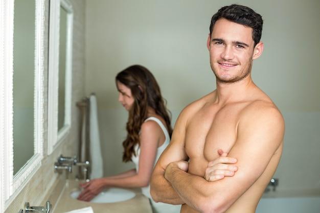 Junger mann, der an der kamera und an frau waschen ihre hände hinter ihm lächelt