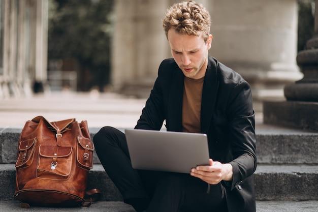 Junger mann, der an einem computer durch die universität arbeitet