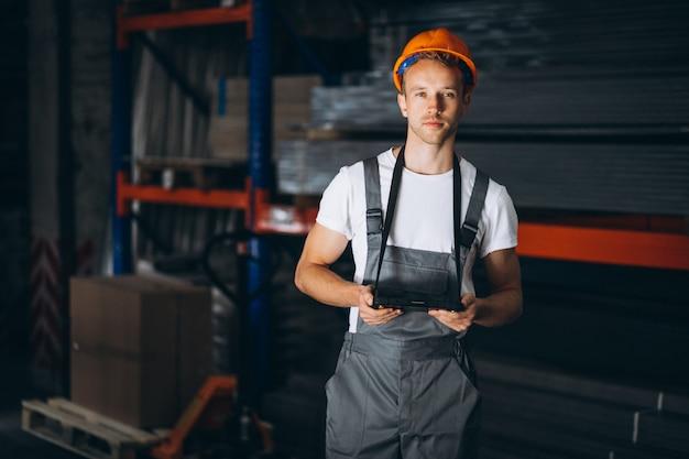 Junger mann, der an einem lager mit kästen arbeitet