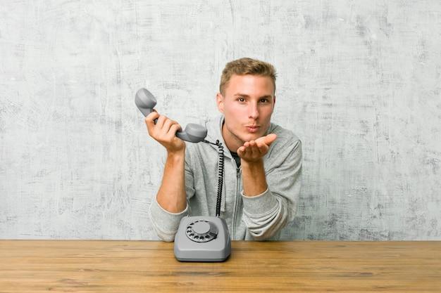 Junger mann, der an faltenden lippen eines weinlesetelefons spricht und palmen hält, um luftkuss zu senden.