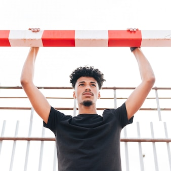 Junger mann, der an fußballziel hält und weg schaut