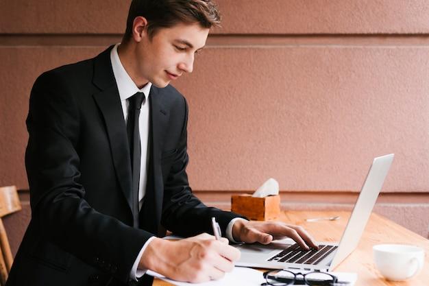 Junger mann, der an laptop im büro arbeitet