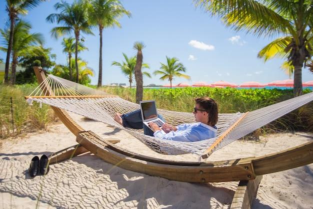 Junger mann, der an laptop in der hängematte am tropischen strand arbeitet